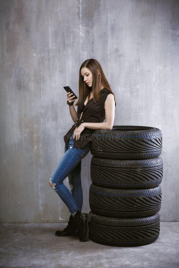 Unga flickan med en mobiltelefon, lutar mot gummihjulen på arkivbilder
