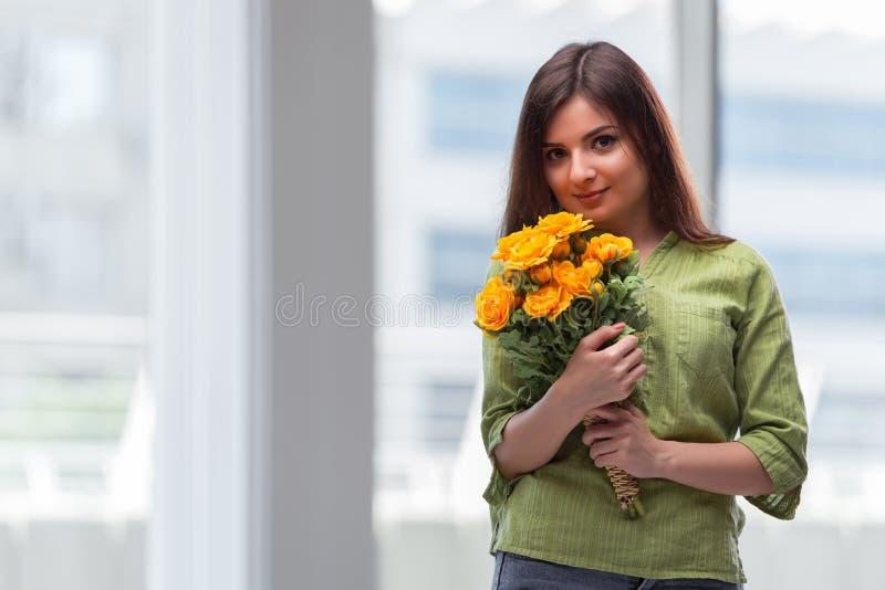 Unga flickan med gåva av blommor royaltyfria foton