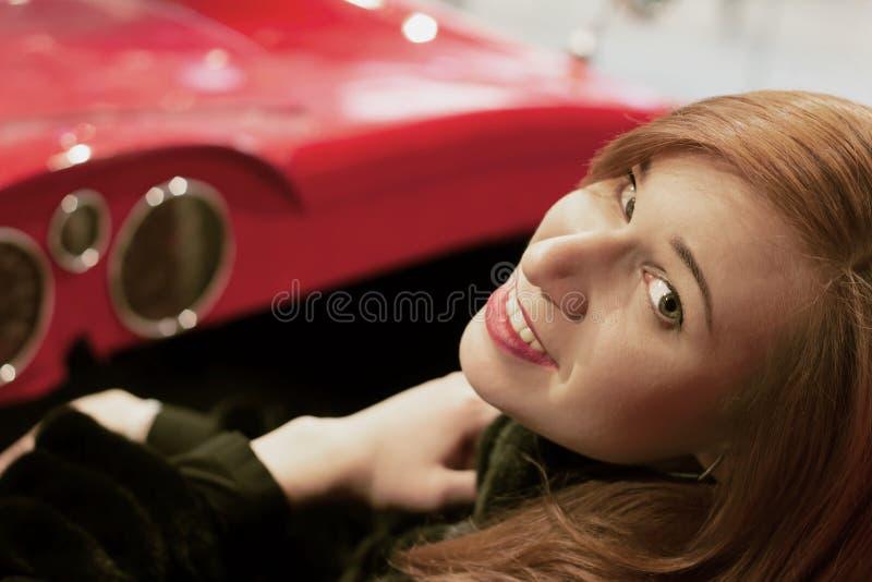 Unga flickan med rött hår sitter i en röd bil med en öppen överkant och blick in i kameran arkivbild
