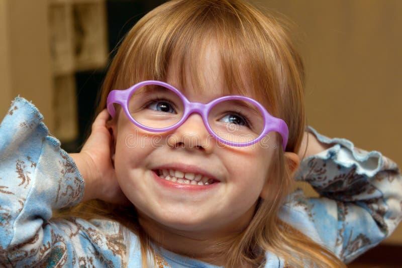 Unga flickan med vindögdhet försöker på nya exponeringsglasramar på arkivfoto