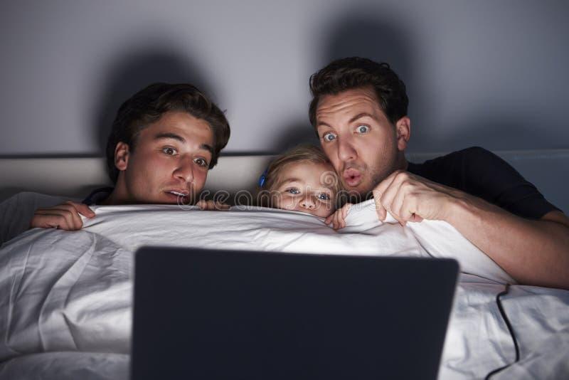Unga flickan och två farsor håller ögonen på den läskiga filmen i säng på bärbara datorn royaltyfria bilder