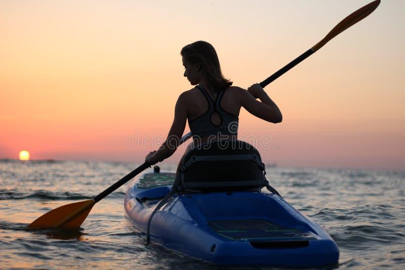 Unga flickan på kajaken hälsar gryningen av solen royaltyfri foto