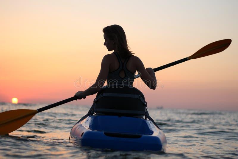 Unga flickan på kajaken hälsar gryningen av solen royaltyfria bilder
