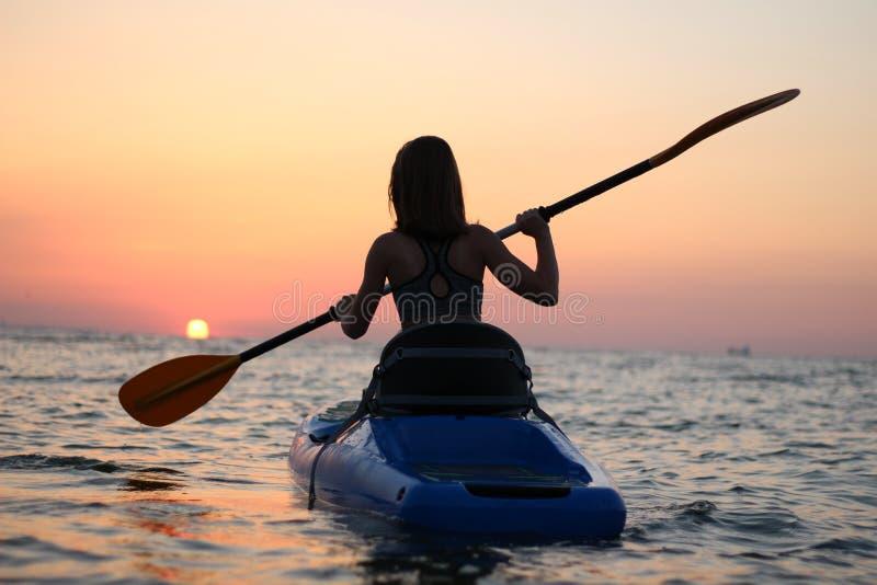 Unga flickan på kajaken hälsar gryningen av solen royaltyfria foton