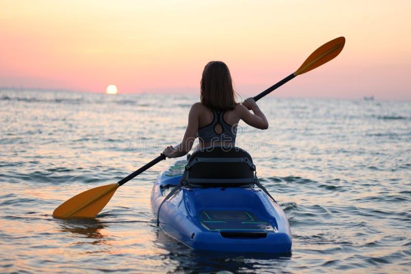 Unga flickan på kajaken hälsar gryningen av solen royaltyfri fotografi