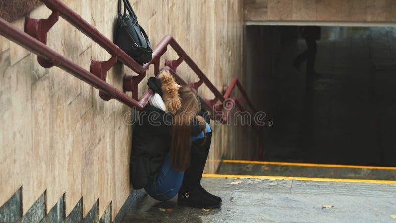 Unga flickan på trappan i det deprimerade sammanträdet för gångtunnelen bara gör framsidan med hans handsandgråt mörkare Höst royaltyfri bild