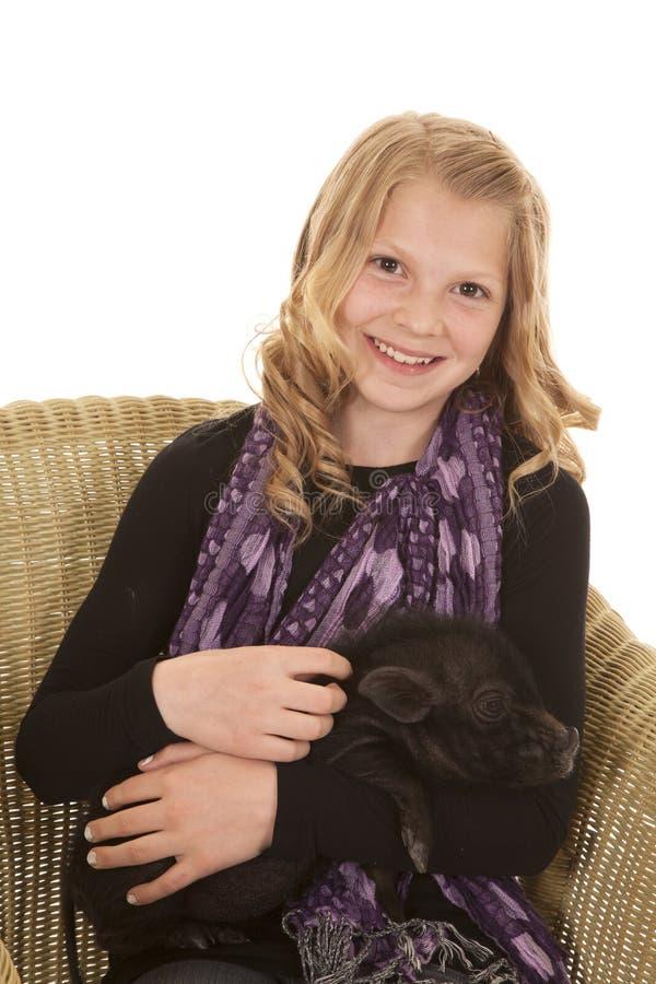 Unga flickan poserar sitter med att se för svin arkivbild