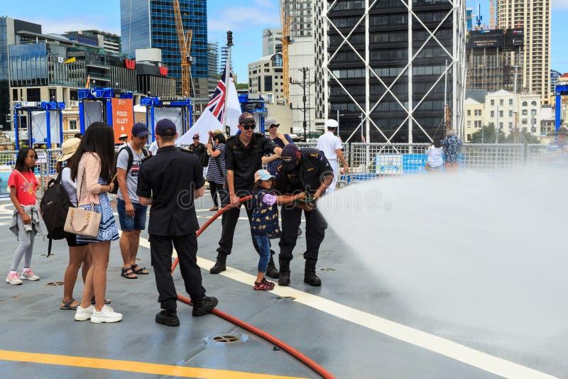 Unga flickan rymmer en bespruta brandslang, med hjälpen av två sjömän arkivbild