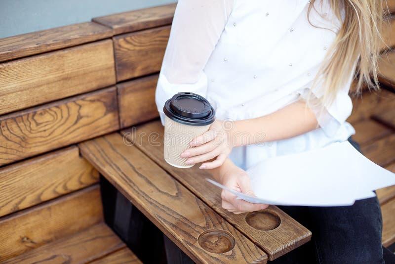 Unga flickan rymmer i hennes hand en pappers- kopp kaffe eller te på en trätabell på en gatamatfestival royaltyfri fotografi
