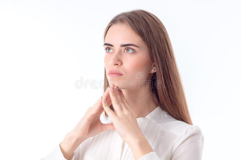 Unga flickan ser bort och tänker isolerat på vit bakgrund arkivfoto