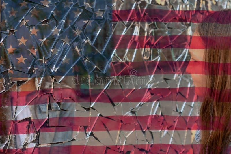 Unga flickan ser i en bruten spegel och visar hennes hand på en spegel mot bakgrunden av amerikanska flaggan royaltyfria bilder