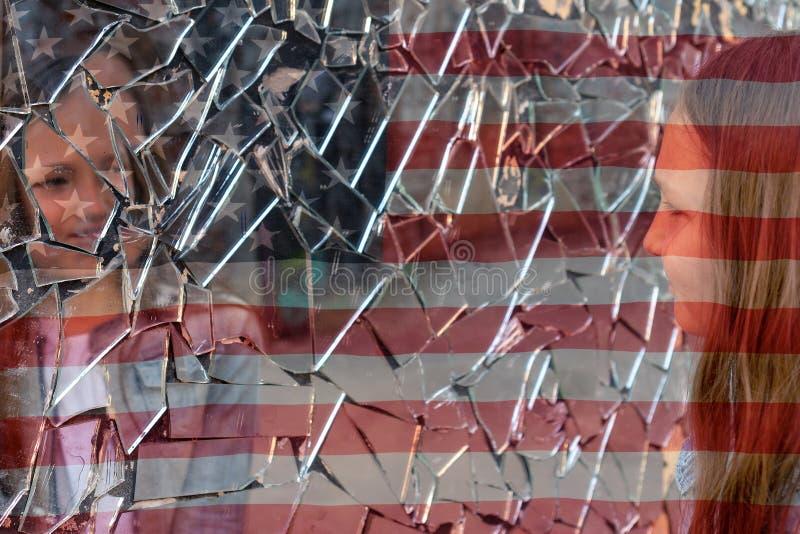 Unga flickan ser i en bruten spegel och visar hennes hand på en spegel mot bakgrunden av amerikanska flaggan arkivfoto