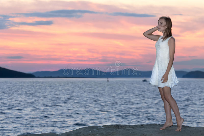 Unga flickan ser solnedgång arkivbilder