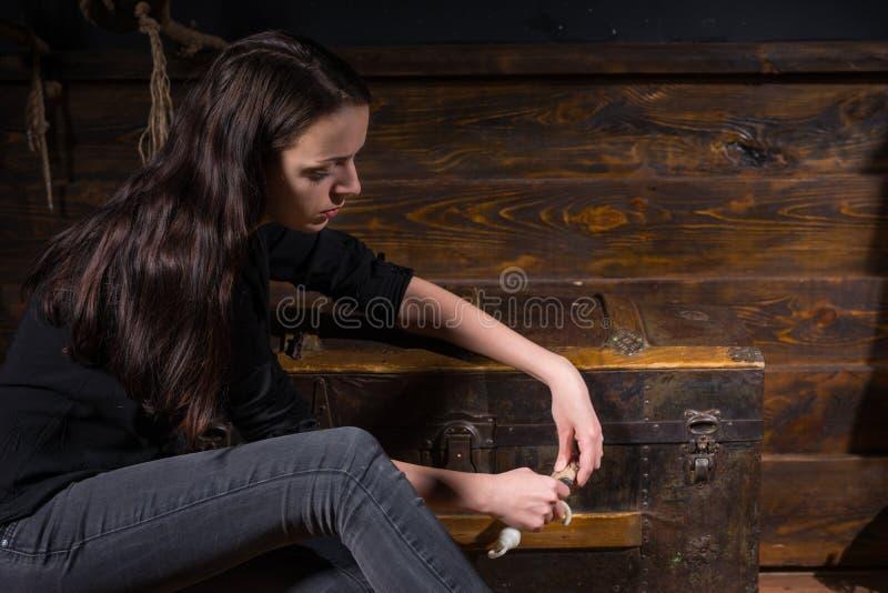 Unga flickan sitter nära en bröstkorg och att försöka att lösa en gåta till fotografering för bildbyråer