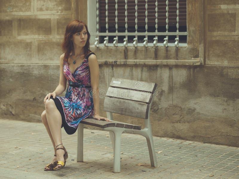 Unga flickan sitter på bänken arkivfoton