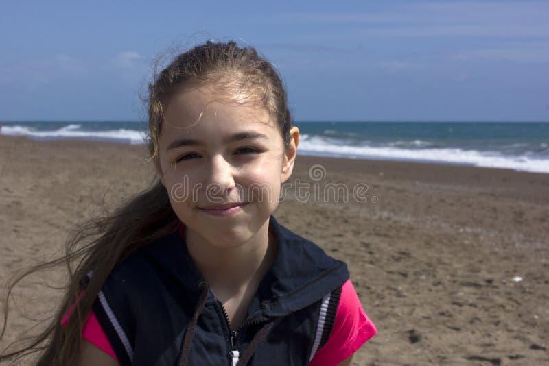 Unga flickan sitter på stranden nära det blåa havet royaltyfri bild