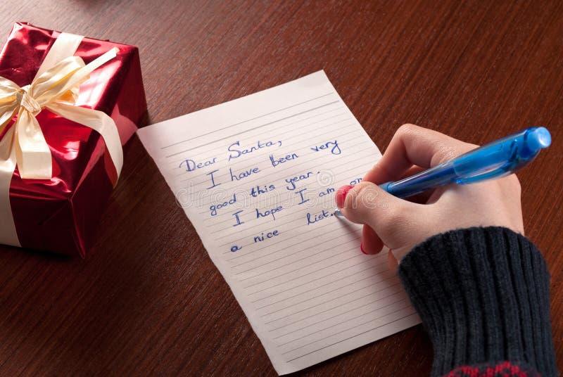 Unga flickan skriver bokstavsönska till Santa Claus på träskrivbordet arkivfoto