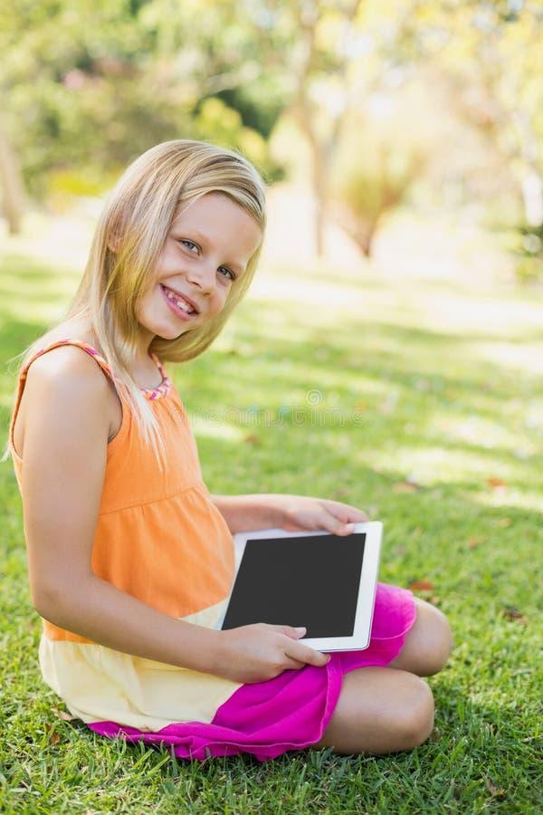 Unga flickan som använder den digitala minnestavlan parkerar in arkivfoto