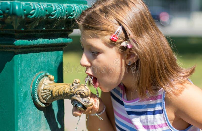 Unga flickan som dricker från en vattenspringbrunn på, parkerar royaltyfri fotografi