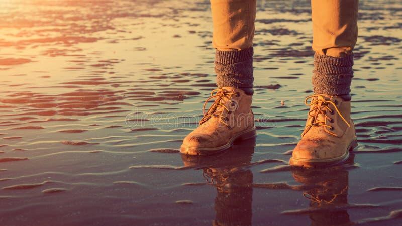 Unga flickan som går på en strand på lågvatten, fot specificerar, äventyrar begrepp arkivbild