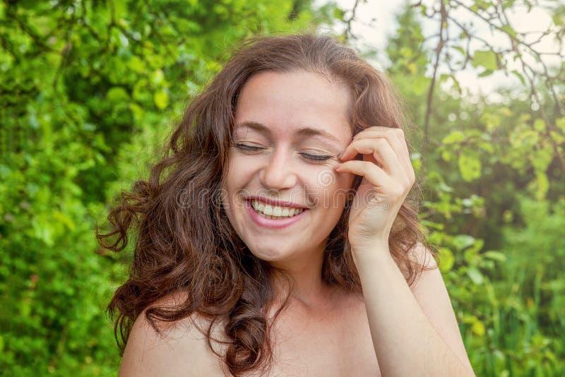 Unga flickan som in ler och skrattar, parkerar royaltyfri fotografi