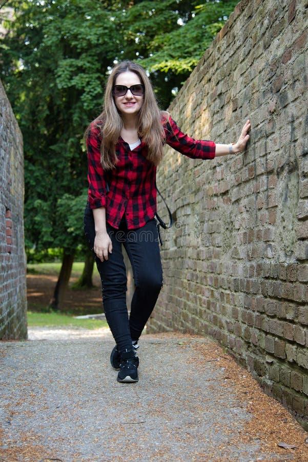 Unga flickan som poserar i parkera, en bakgrund för tegelstenvägg royaltyfri fotografi