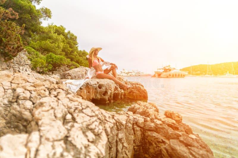 Unga flickan som sitter på, vaggar bara och se havet royaltyfria bilder