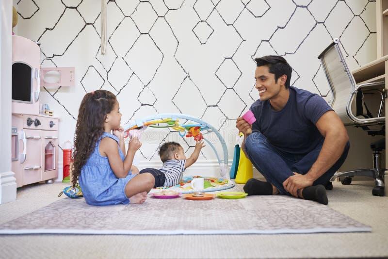 Unga flickan som spelar tebjudningen med farsan som sitter p? golvet, behandla som ett barn brodern p? en lek som ?r matt bredvid royaltyfria bilder