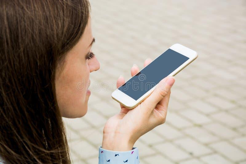 Unga flickan som talar på en mobiltelefon utanför i, parkerar på speakerphonen arkivbilder