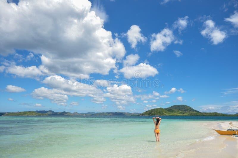 Unga flickan står i grunt vatten som ser horisonten arkivfoton