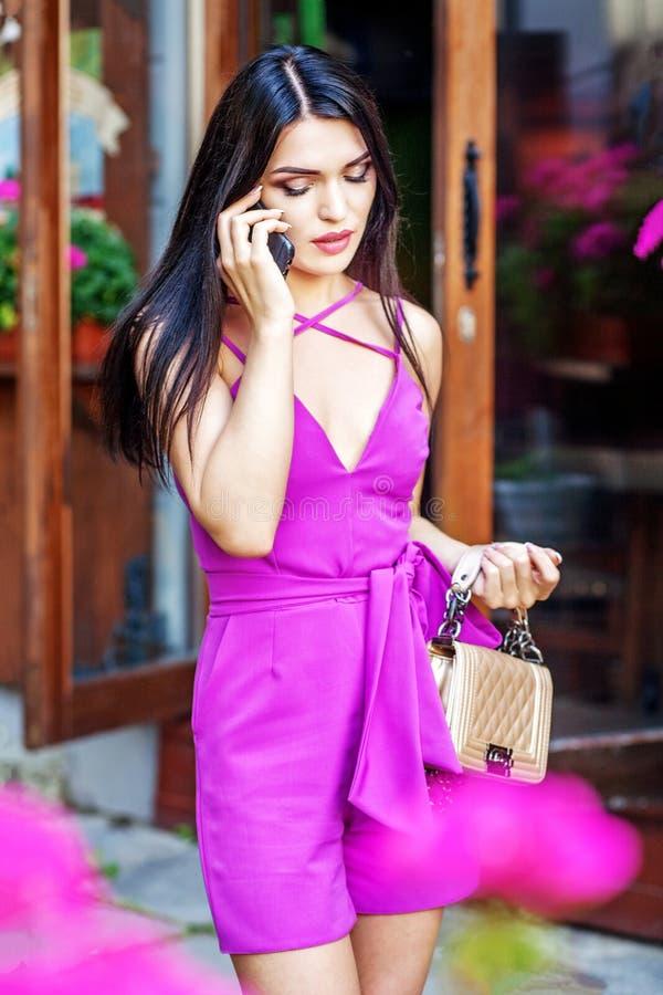 Unga flickan talar vid telefonen i gatan Begreppslivsstil och royaltyfri foto
