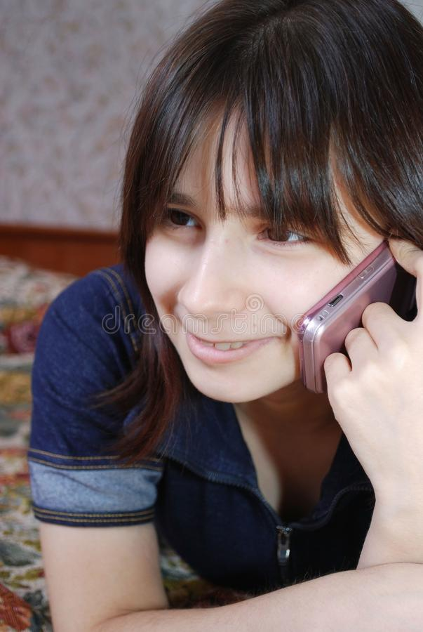 Unga flickan tonåringen ligger på en säng och talar vid telefonen arkivbild