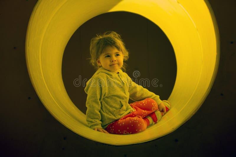 Unga flickan tycker om att klättra till och med en tunnel i en lekplats för barn` s royaltyfri bild