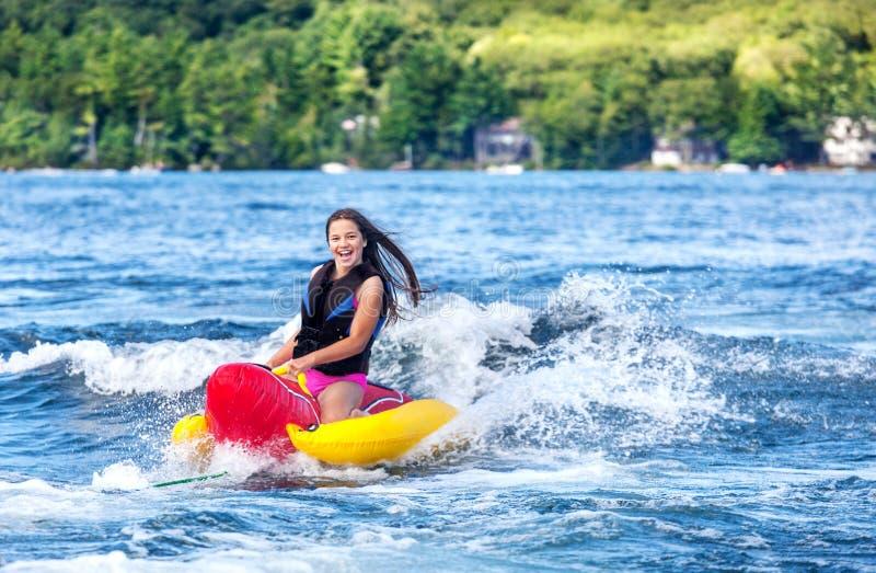 Unga flickan tycker om rör på sjön royaltyfri fotografi