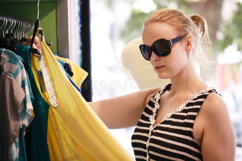 Unga flickan väljer klänningen shoppar in royaltyfria bilder