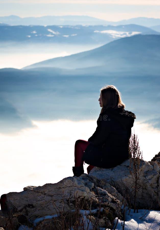 Unga flickan vilar på bergöverkanten royaltyfri fotografi