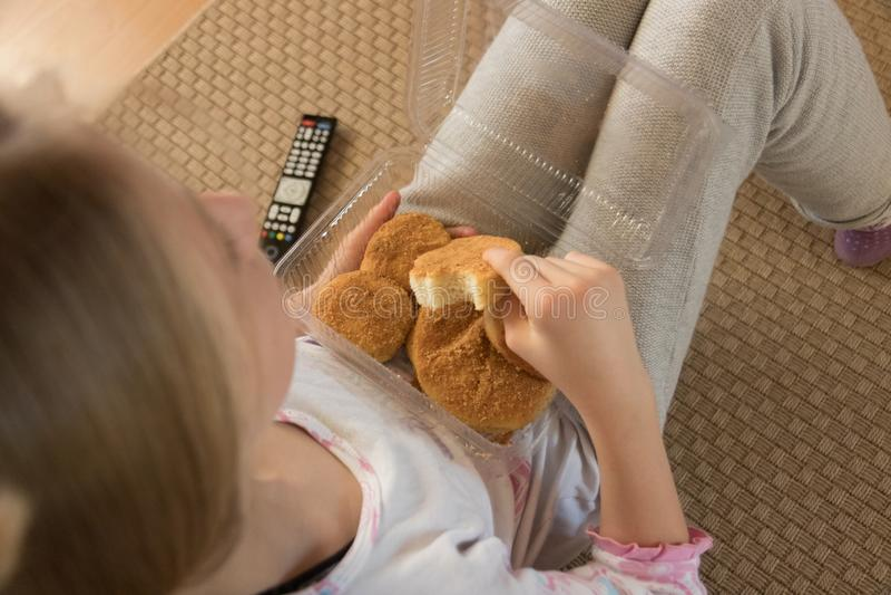 Unga flickor avslappnar och äter frukost på sitt vardagsrum medan de tittar på Tv fotografering för bildbyråer