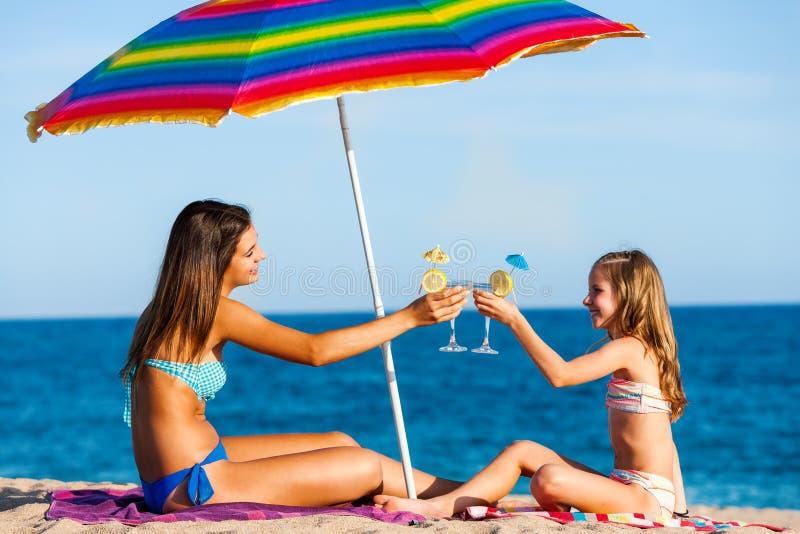 Unga flickor på sommarferie med coctailar royaltyfria bilder