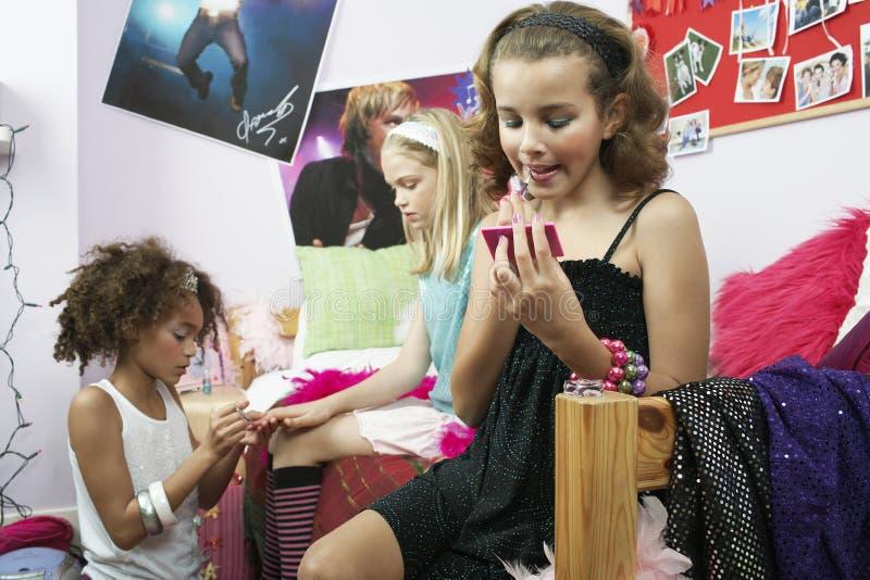 Unga flickor som applicerar makeup i sovrum arkivbilder