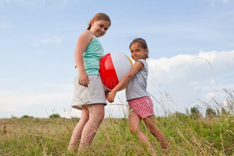 Unga flickor som spelar med en boll utomhus royaltyfria foton