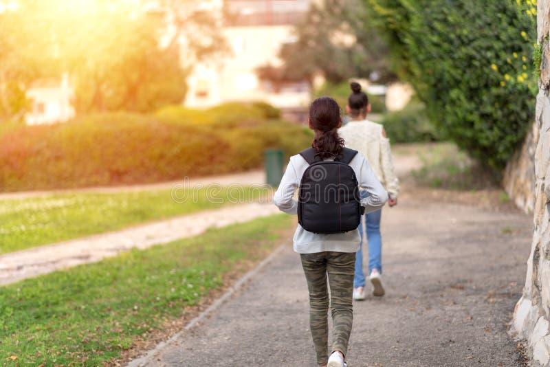 Unga flickor som utomhus går i sommarstadsgata på solnedgång- eller soluppgångtid royaltyfri fotografi