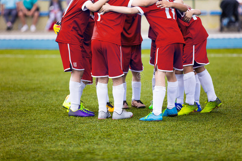 Unga fotbollfotbollspelare i röd sportswear Ungt sportlag Fotbollsmatch för ungar fotografering för bildbyråer