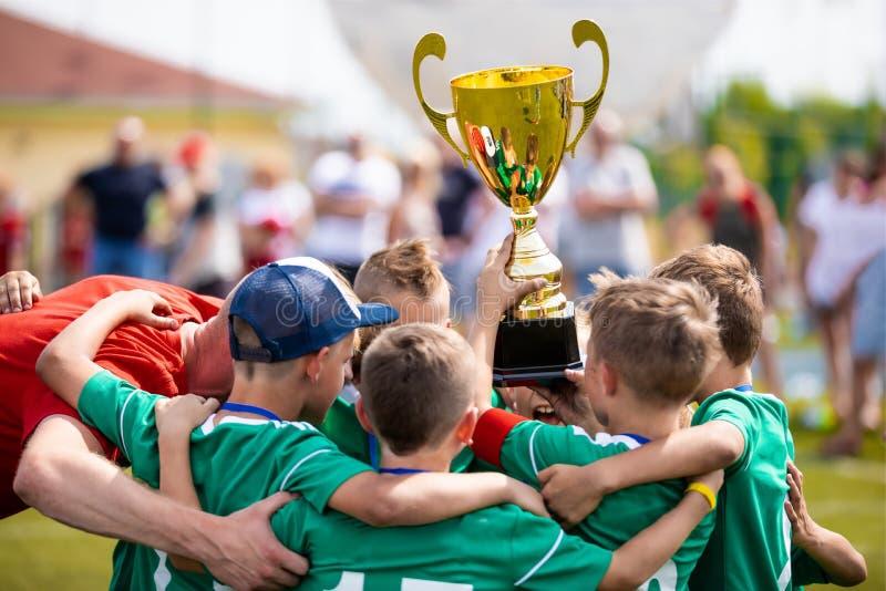 Unga fotbollspelare som rymmer trofén Pojkar som firar fotbollfotbollmästerskap royaltyfri bild