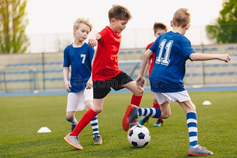 Unga fotbollsspelare som sparkar bollen på fotbollfält Fotbollhorisontalbakgrund arkivbild