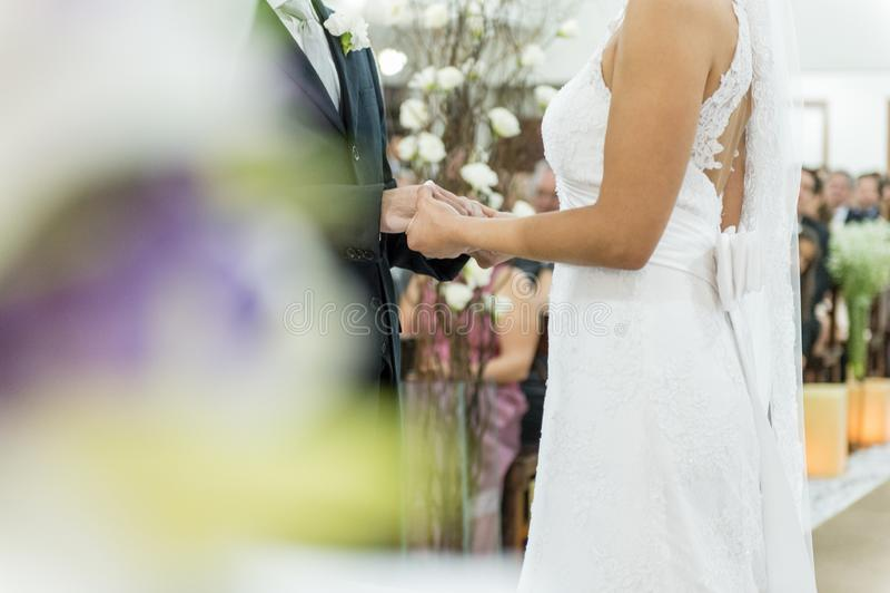 Unga gift parinnehavhänder, ceremonibröllopdag royaltyfria bilder