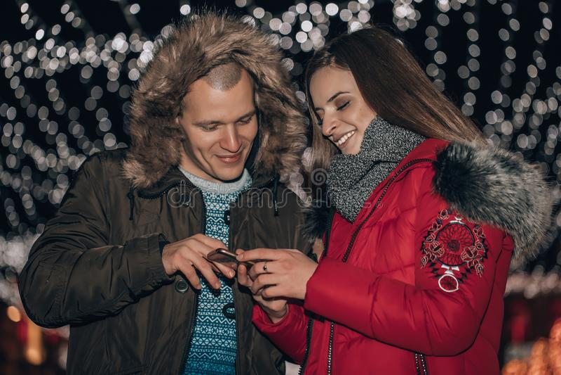 Unga glada par som delar media i en smart telefon som står i en stad, på natten royaltyfria foton