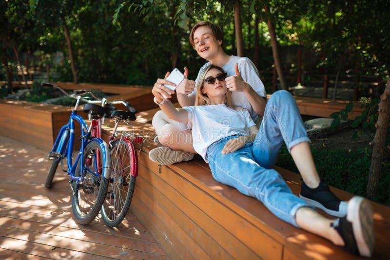 Unga glade par som spenderar tid parkerar in, med närliggande cyklar Le pojkesammanträde på bänk parkera in med den nätta flickan fotografering för bildbyråer