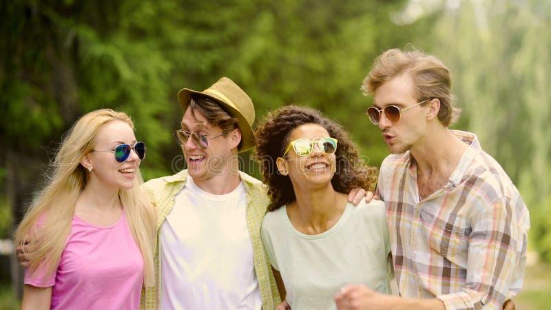 Unga glade vänner som tillsammans skrattar och att ha bra helg parkerar in, avkoppling royaltyfri bild