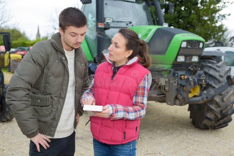 Unga gladlynta lantbrukpar som kontrollerar deras traktor för skörd royaltyfri bild