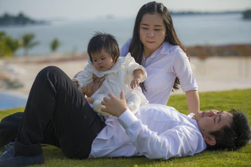 Unga gladlynta och söta fru- och makepar med modern och fadern som spelar med den lilla dottern i asiatisk kinesisk familj royaltyfri fotografi